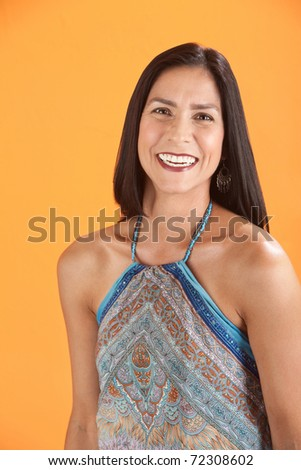 Latina woman with a big smile on an orange background