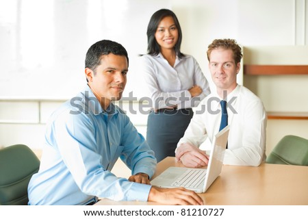 Latino businessman leader sitting at desk on laptop in conference room, meeting with diverse team of business people, attractive Asian woman and Caucasian male looking at camera. Horizontal