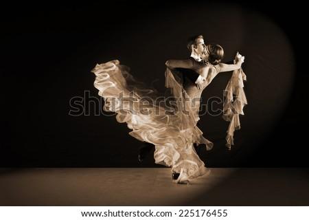 Latino dancers in ballroom against black background - stock photo