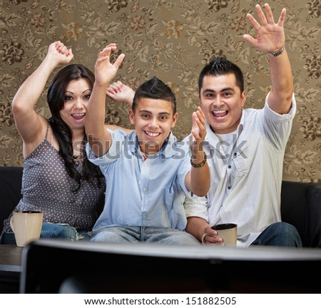 Latino family of three celebrating in front of television - stock photo