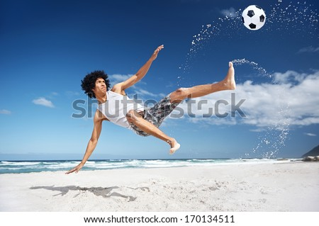 Latino Hispanic man doing bicycle kick on beach with soccer ball - stock photo