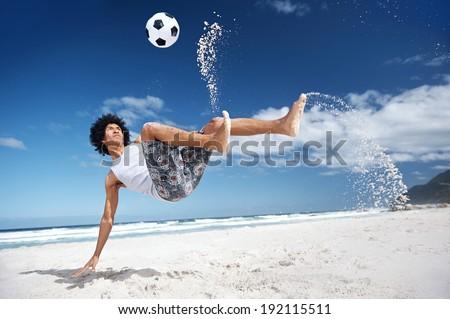 Latino Hispanic man doing bicycle kick on beach with soccer ball - stock photo