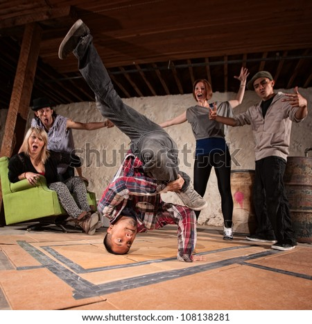 Latino man spinning on his head in break dancing battle - stock photo