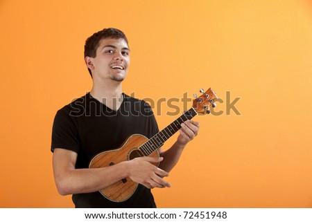 Latino teen playing a ukulele on an orange background - stock photo