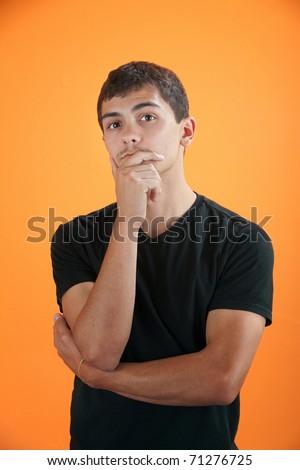 Latino teenage boy on orange background in deep thought - stock photo