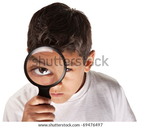 Latino youth looking through a magnifying glass - stock photo