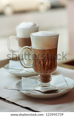 Latte and macchiato coffee cocktail in a cafe with spoon - stock photo