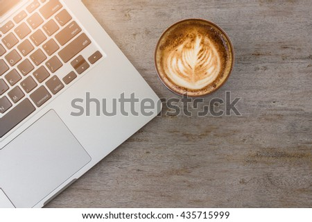 latte art art and laptop on wooden desk in coffee shop. - stock photo