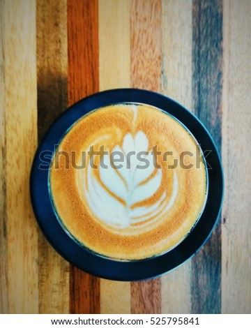 latte art coffee on stripped wooden table