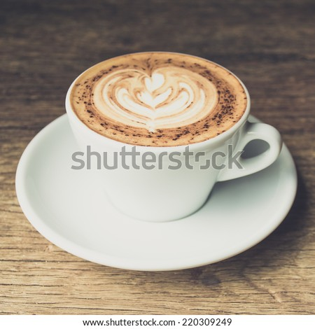 Latte art on cappuccino coffee cup with vintage filter effect. - stock photo