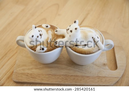 Latte coffee topping made by milk foam top on the cup of hot coffee . place on the wood table - stock photo