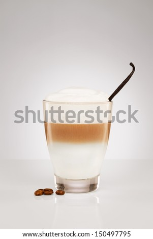 latte macchiato with a vanilla bean and coffee beans on gray background - stock photo