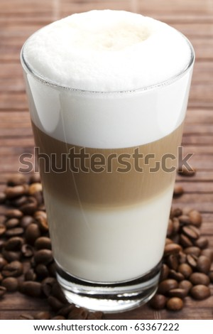 latte macchiato with coffee beans on wooden background - stock photo