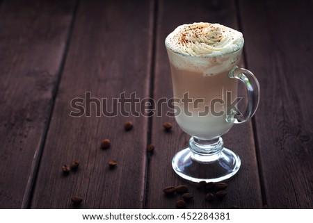 Latte Macchiato with whipped cream on dark wooden background - stock photo