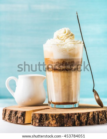 Latte macchiato with whipped cream, serving silver spoon and white pitcher on wooden round board over blue painted wall background, selective focus, vertical composition - stock photo