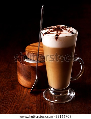 latte mug on a wooden table with a spoon and sugar - stock photo