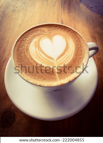 Latte or cappuccino coffee on wooden desk with retro filter effect  - stock photo