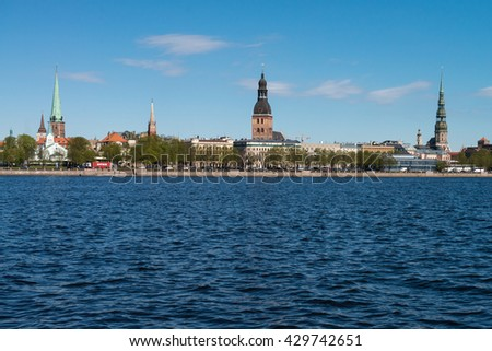 LATVIA / RIGA: panoramic view on the embankment of the Daugava River: Riga castle, Riga Cathedral, Saint Peters Church, TV tower and bridges. - stock photo