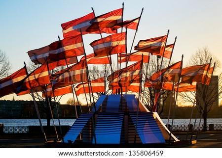 Latvian flags near the river Daugava - stock photo