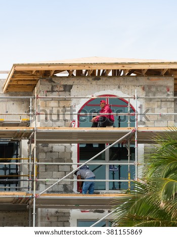LAUDERDALE BY THE SEA, FL - JANUARY 13: Two unidentified workers are working on construction of a new building in Lauderdale By The Sea, Florida on January 13, 2016 - stock photo