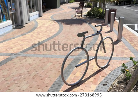 LAUDERDALE-BY-THE-SEA, FL, USA - APRIL 7, 2014: One silver metal bike rack in the shape of a bike mounted on a brick sidewalk on a sunny day. A silver bike rack in bicycle shape on a brick sidewalk - stock photo