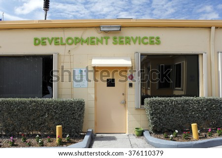 Lauderdale-by-the-Sea, FL, USA - May 16, 2015: Development Services building exterior front entrance. Development Services signs and office entrance on a sunny day.  - stock photo
