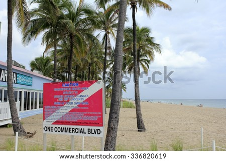 Lauderdale-By-The-Sea, FL, USA - September 20, 2014: Diver symbol caution sign One Commercial Boulevard. Beach view, warning sign and Aruba restaurant near trees. - stock photo