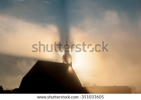 LAUFEN, BAVARIA/GERMANY - DECEMBER 10, 2015: Silhouette of Stiftskirche and mirage shadow in fog on a blue sky sunset - stock photo