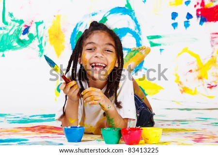 Laughing African American girl lying with a paintbrush