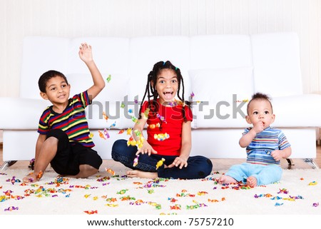 Laughing african american kids playing with candies - stock photo