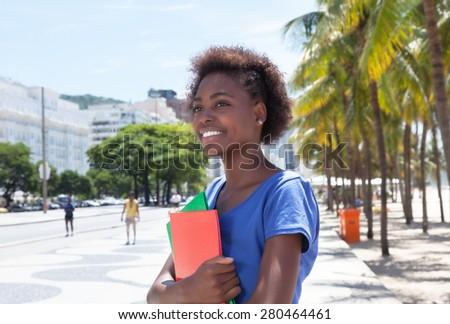 Laughing african american student in the city - stock photo