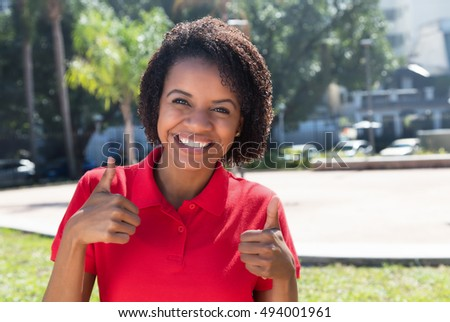 Laughing african american woman showing thumb in the city