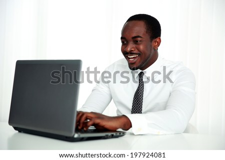 Laughing african man using laptop in office - stock photo