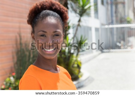 Laughing african woman in a orange shirt - stock photo