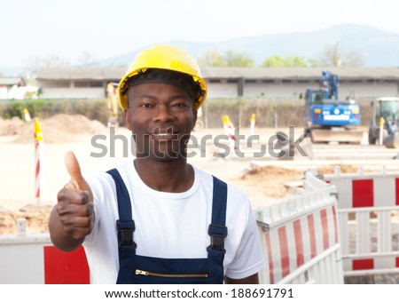 Laughing african worker at construction site showing thumb up  - stock photo