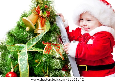 Laughing attractive baby decorating Christmas tree - stock photo