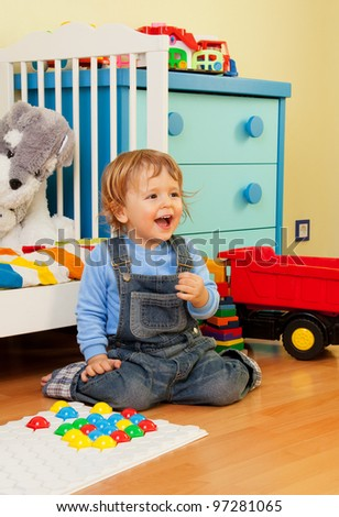 Laughing baby assemble with mosaic sitting in the bedroom - stock photo