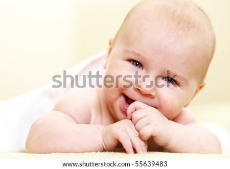 laughing baby boy lying indoor - stock photo