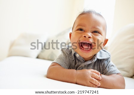Laughing Baby Boy Lying On Tummy At Home - stock photo