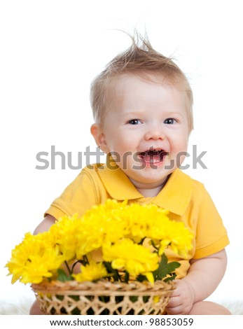 laughing baby boy with yellow flowers in basket - stock photo