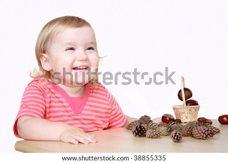 Laughing baby girl playing with cones and chestnuts