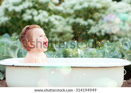 Laughing baby girl taking bath outdoors. Happy child. Childhood.  - stock photo