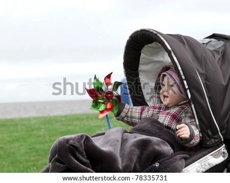 laughing baby in a stroller - stock photo