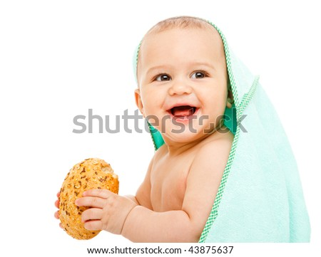 Laughing baby in towel holding a bun - stock photo