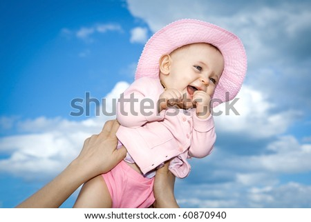 Laughing baby jumping against a blue sky. - stock photo