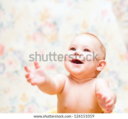 Laughing baby looks up and hands up - stock photo