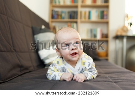laughing baby on sofa, Beautiful smiling cute baby, expressive adorable happy child in child's room, blurry background