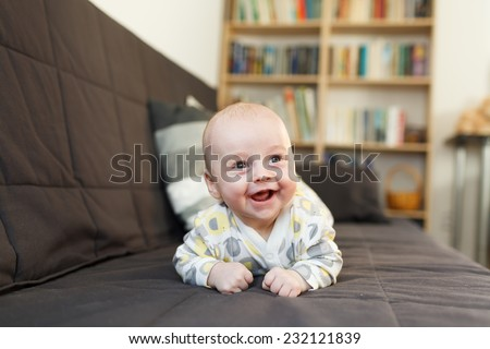 laughing baby on sofa, Beautiful smiling cute baby, expressive adorable happy child in child's room, blurry background - stock photo