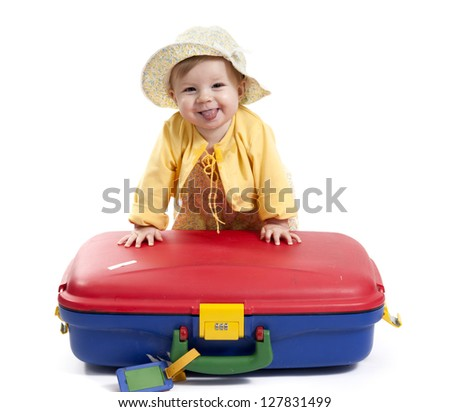laughing baby with red and blue suitcase, isolated on white background