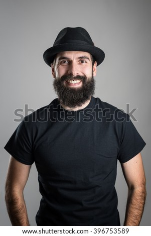 Laughing bearded hipster wearing black t-shirt and hat looking at camera.  Headshot portrait over gray studio background with vignette.  - stock photo